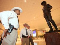 Texas Ranger David Armstrong, left, looks over the re-installed 'One Riot, One Ranger' statue by Waldine Tauch, at the main lobby inside Love Field airport, on March 12, 2013 in Dallas.