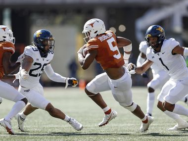 AUSTIN, TEXAS - NOVEMBER 07: Bijan Robinson #5 of the Texas Longhorns carries the ball defended by Tony Fields II #1 of the West Virginia Mountaineers and Sean Mahone #29 int he first quarter at Darrell K Royal-Texas Memorial Stadium on November 07, 2020 in Austin, Texas.