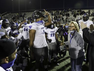 Mansfield assistant athletic director Tammy Lusinger presents the Class 5A Division I Region I Championship trophy to the Summit football team after a win against Colleyville Heritage at Bearcat Stadium in Aledo, Texas, Saturday, December 26, 2020. (Elias Valverde II / Special Contributor)