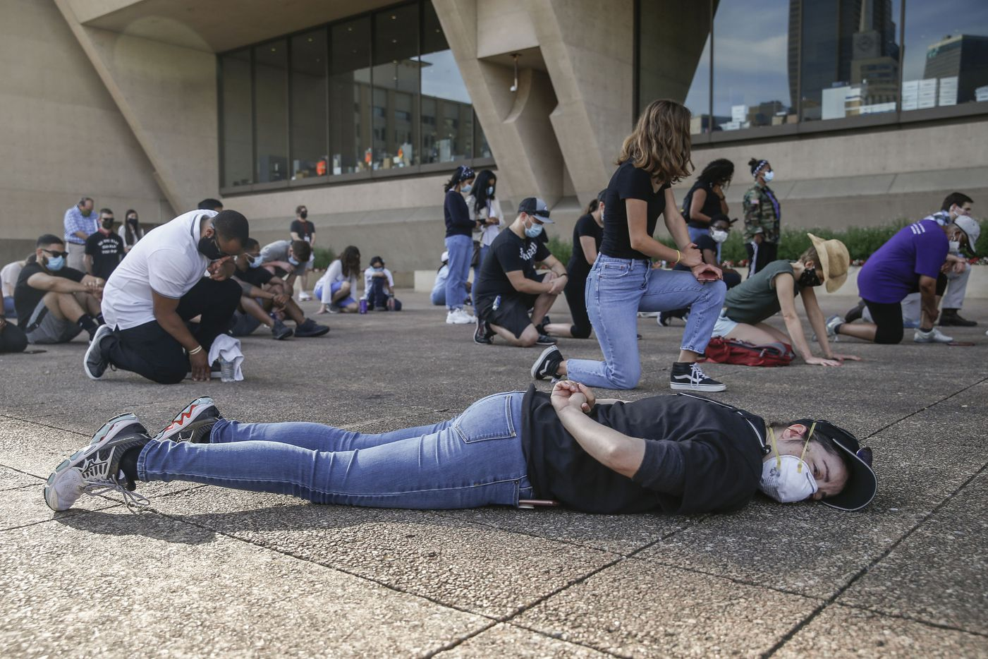 Community members kneel and lay on the ground for an 8 minute and 46 second a moment of silence during a memorial service for George Floyd on Friday, June 5, 2020 at City Hall in Dallas.