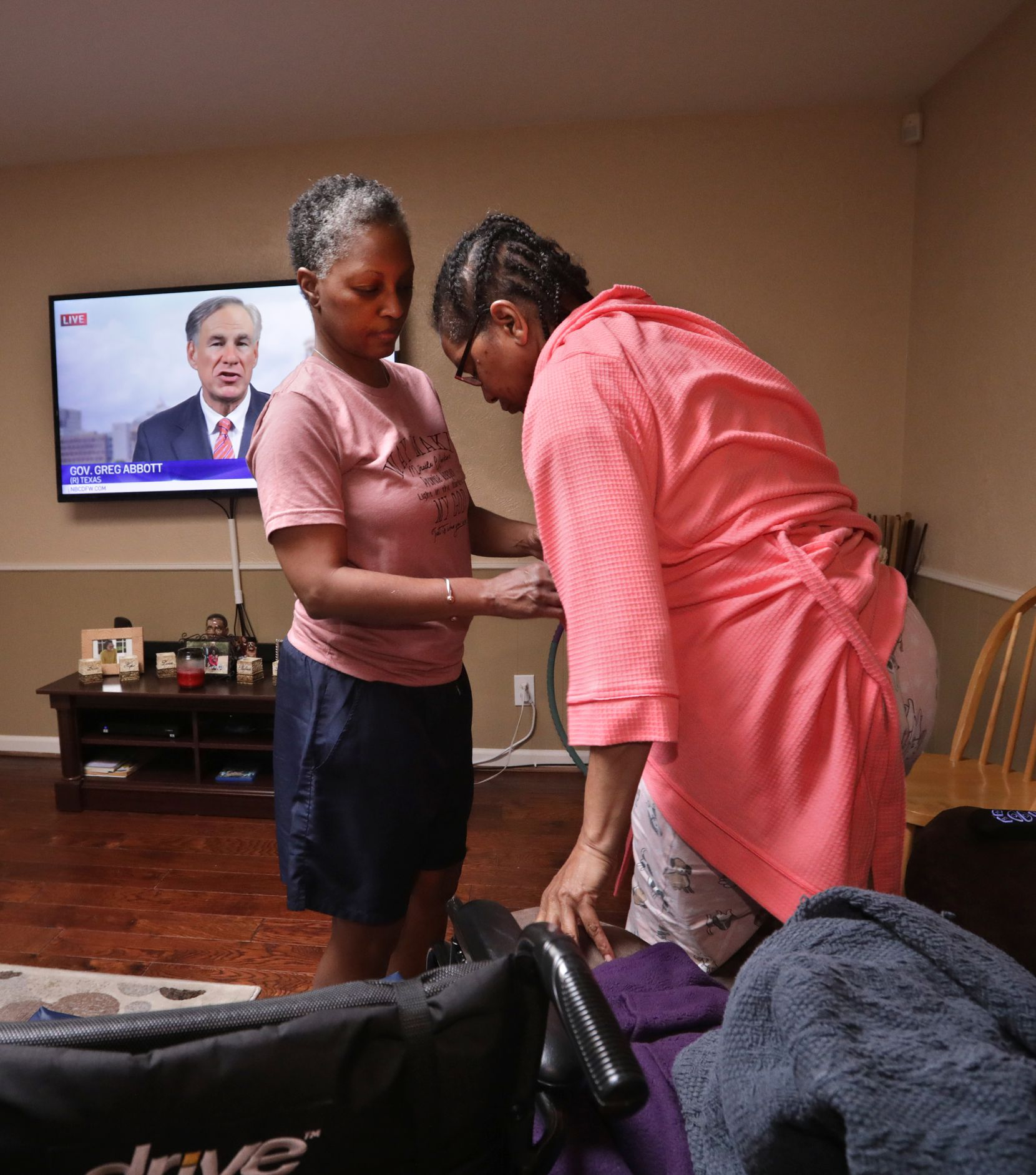 Bea Brown (left) assists her sister Beth in moving between her wheelchair and a chair at their home.