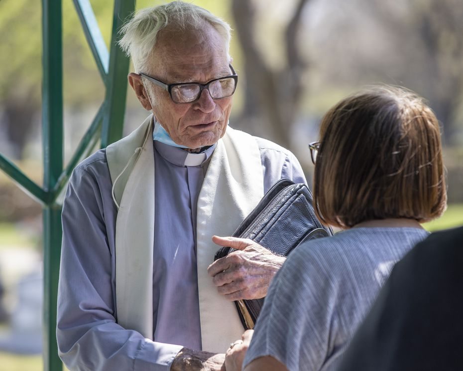 """The Rev. Timothy Gollob speaks with Judy Lewis at the funeral of his longtime friend and Lewis' father, Frank """"Zip"""" Krajca, at Calvary Hill Cemetery in Dallas on March 27."""