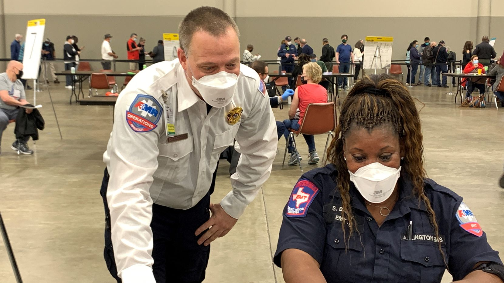Michael Marsh, operations manger at American Medical Response Arlington, chats with AMR EMT Sylvia Bailey at the Arlington COVID-19 vaccination site. Marsh has been supporting the vaccination operation by helping register and vaccinate people.
