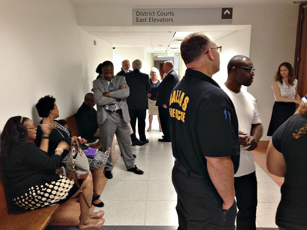 St. Philip's officials (including headmaster Terry Flowers, arms folded in gray suit), code enforcers and 3006 Holmes St. residents awaited what turned out to be a brief and frustrating hearing in Judge Dale Tillery's courtroom Wednesday.