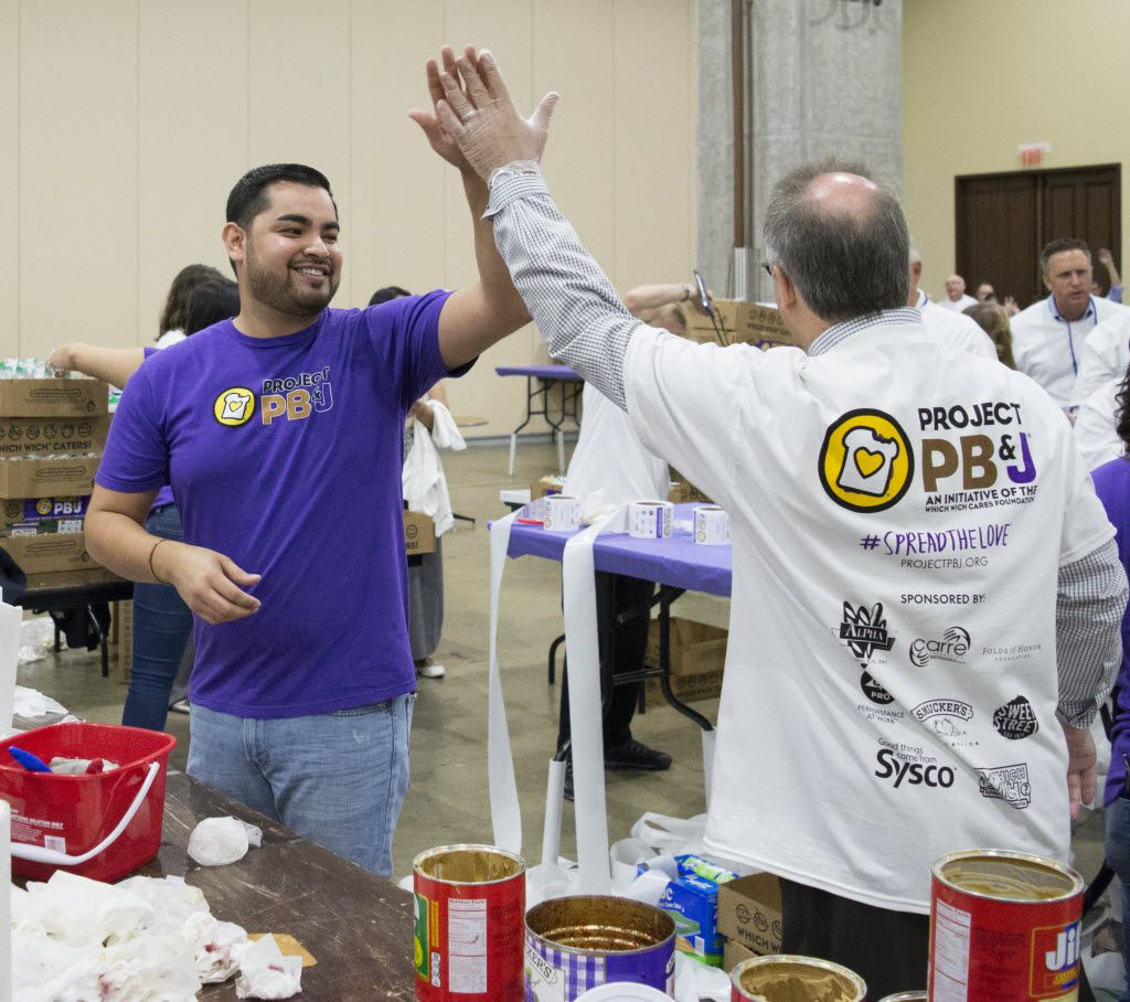 Spread the Love team captain Jaime Enriquez high fives one of the other volunteers at the end of the one hour Guinness World Record Spreading Party where volunteers made 39303 PB&J sandwiches.