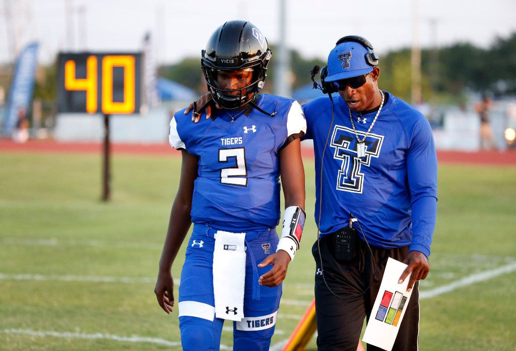 Trinity Christian-Cedar Hill offensive coordinator Deion Sanders, right, talks to his son, Shedeur Sanders (2) prior to their high school football game against the Episcopal School of Dallas in Cedar Hill, Texas, on September 1, 2017.