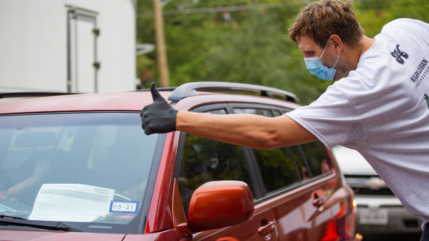 Former Dallas Mavericks player Dirk Nowitzki gives a driver a thumbs up before loading their car with food during the Center Table Fall Harvest food drive at the Mark Cuban Center in Dallas on Thursday, Oct. 22, 2020.