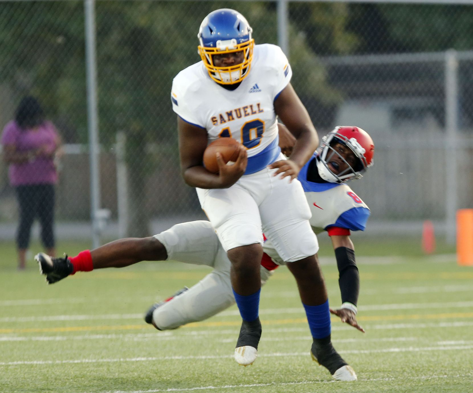 Samuell QB Roie White (10) evades Spruce defender Kelvin Jones (8) during the first half of the season opening high school football game between against Samuell and Spruce High at Pleasant Grove Stadium in Dallas on Friday, August 27, 2021. (John F. Rhodes / Special Contributor)