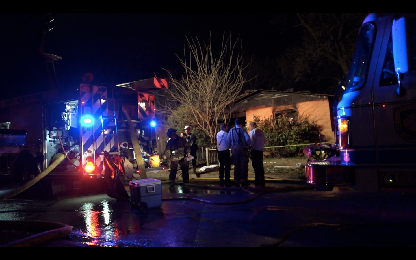 Fire officials survey the scene outside a home that burned Wednesday morning in Fort Worth. Two people inside the home were injured.