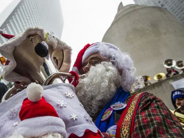 Warren Brooks, who is dressed as Santa Claus, performs with over 250 other tuba, sousaphone and euphonium players during the 39th annual Tuba Christmas on Friday, December 23, 2016 at Thanksgiving Square in downtown Dallas. (Ashley Landis/The Dallas Morning News)
