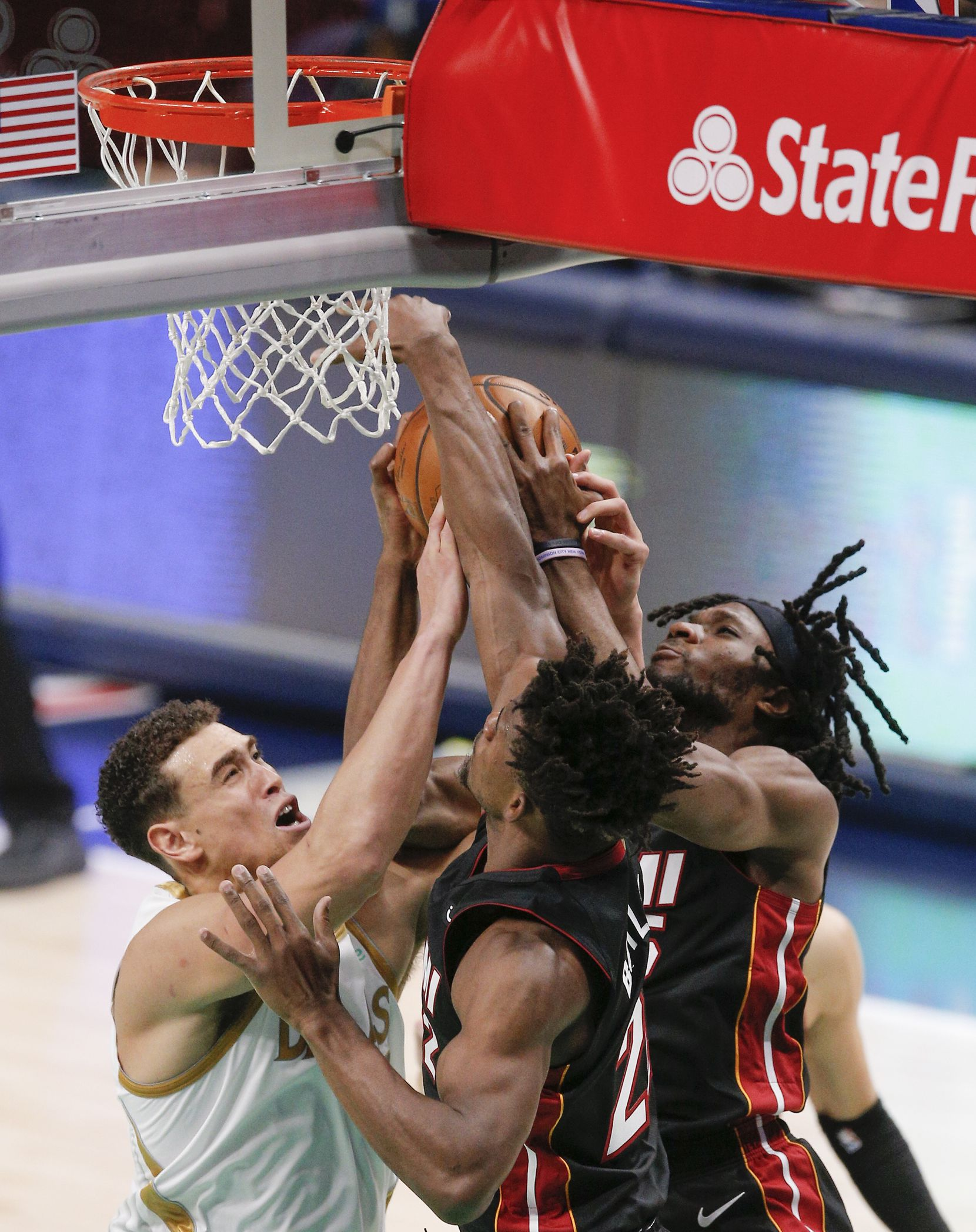 Dallas Mavericks forward Dwight Powell, left, battles Miami Heat forwards Jimmy Butler, and Precious Achiuwa (5) for the ball during the first half of an NBA basketball game, Friday, January 1, 2021. (Brandon Wade/Special Contributor)
