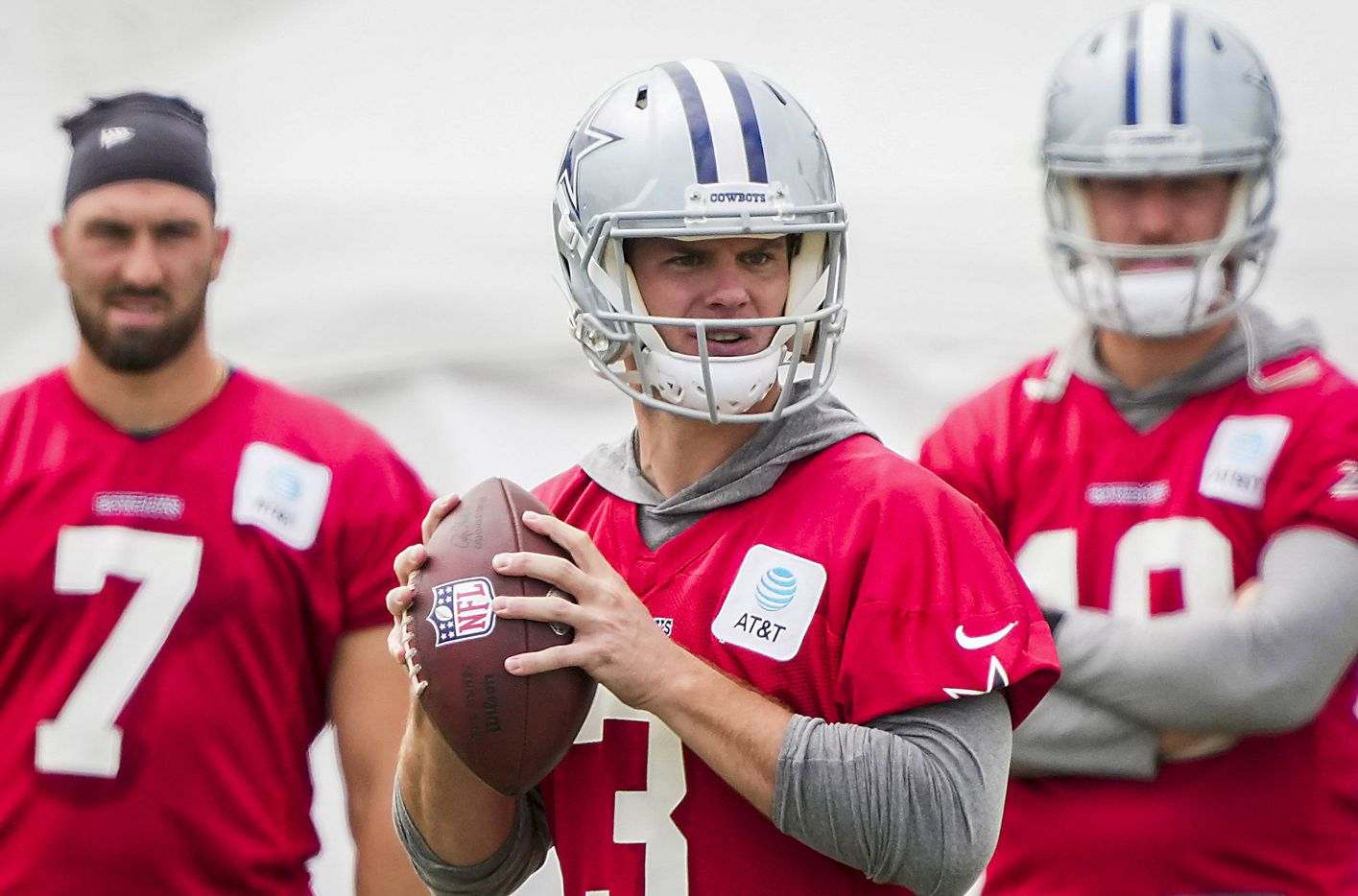 Dallas Cowboys quarterback Garrett Gilbert (3) throws a pass as fellow quarterbacks Ben DiNucci (7) and Cooper Rush (10) look on during a practice at training camp on Saturday, July 24, 2021, in Oxnard, Calif.