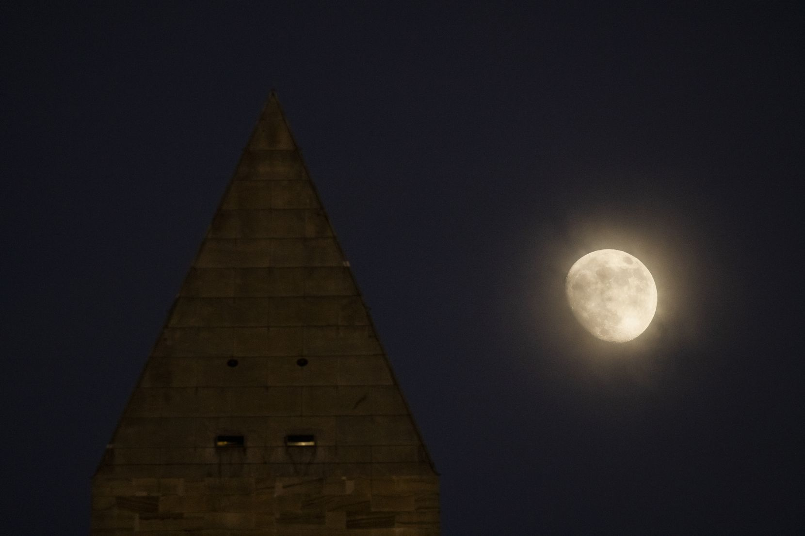 The Washington Monument is shown as the moon rises in Washington, D.C., on Saturday, Dec. 26, 2020.