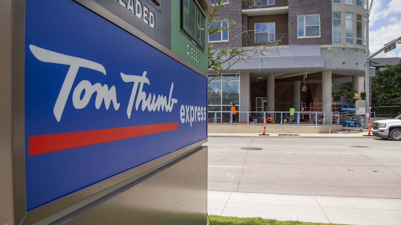 A sign in the foreground for a Tom Thumb Express convenience store sits across the street from the site of a new Tom Thumb store under construction at Live Oak and Texas Street in Dallas on Wednesday. The new store is set to open this fall.