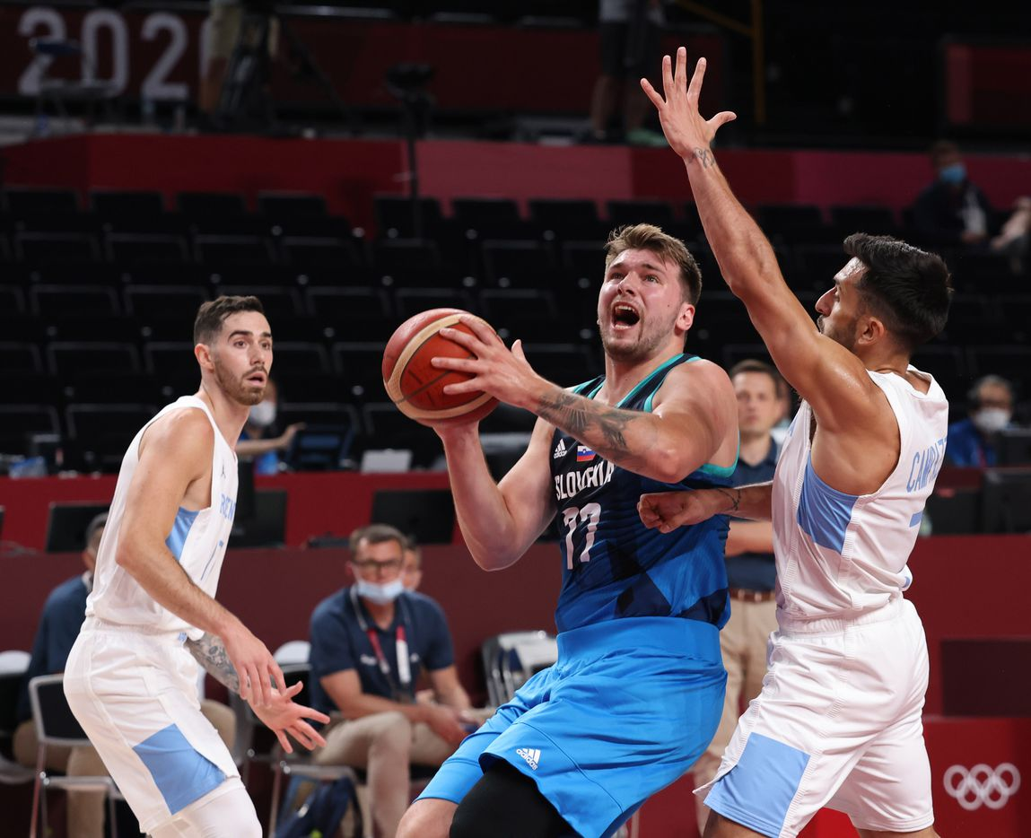 Slovenia's Luka Doncic (77) attempts a shot in front of Argentina's Facundo Campazzo (7) in the first half of play during the postponed 2020 Tokyo Olympics at Saitama Super Arena on Monday, July 26, 2021, in Saitama, Japan. Slovenia defeated Argentina 118-100. (Vernon Bryant/The Dallas Morning News)