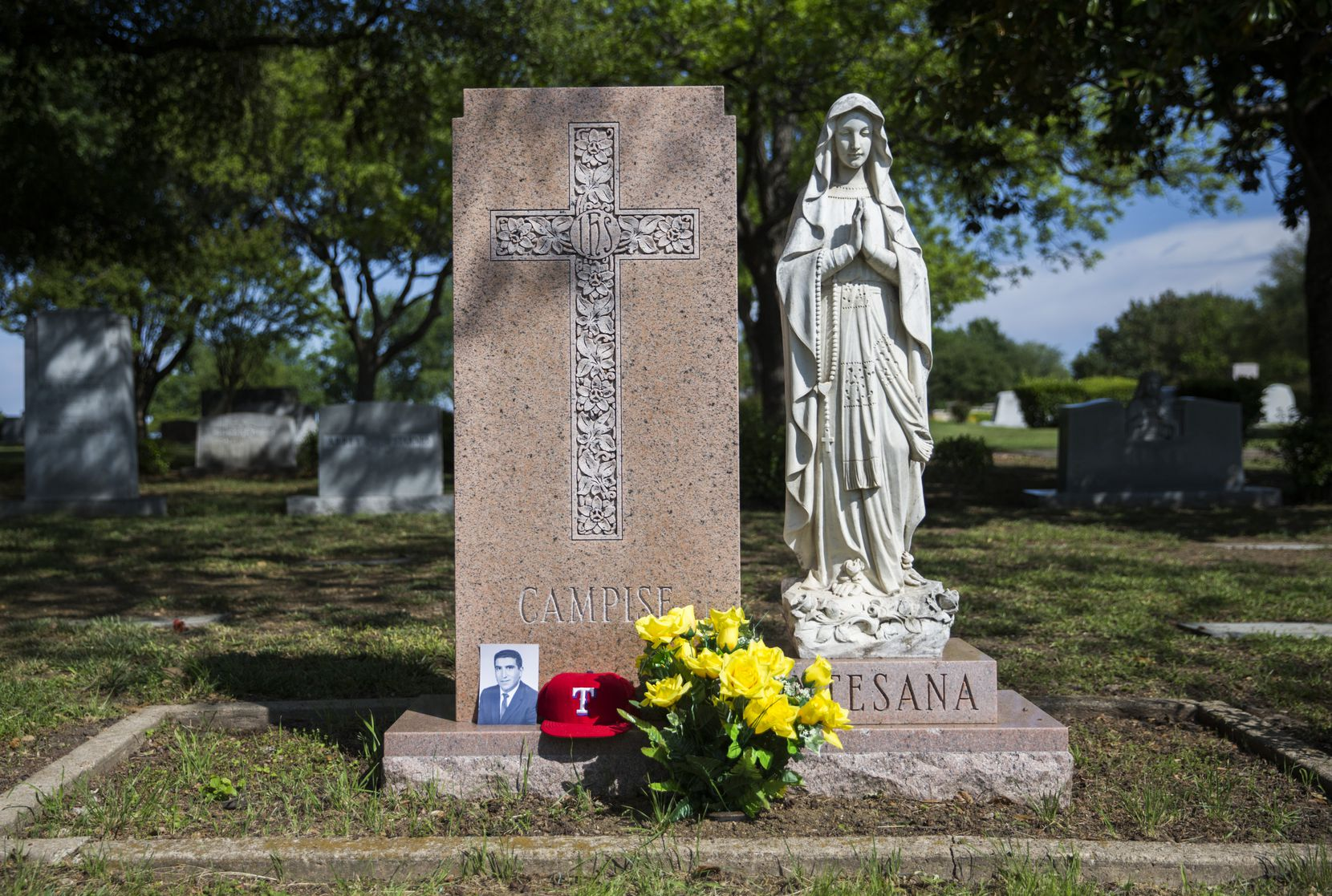 A portrait of Frank Campise and his cherished red Texas Rangers baseball cap rested near his grave at Calvary Hill Cemetery in Dallas on April 18. His wife, Lucy, and daughter, Mary Frances, brought the portrait and ballcap to honor him as photos were taken for this story.