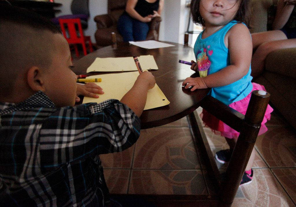 Two children, both from El Salvador, take time to draw in a southern Dallas home. They both came in the increased flow from Central America. (Ben Torres/Special Contributor)