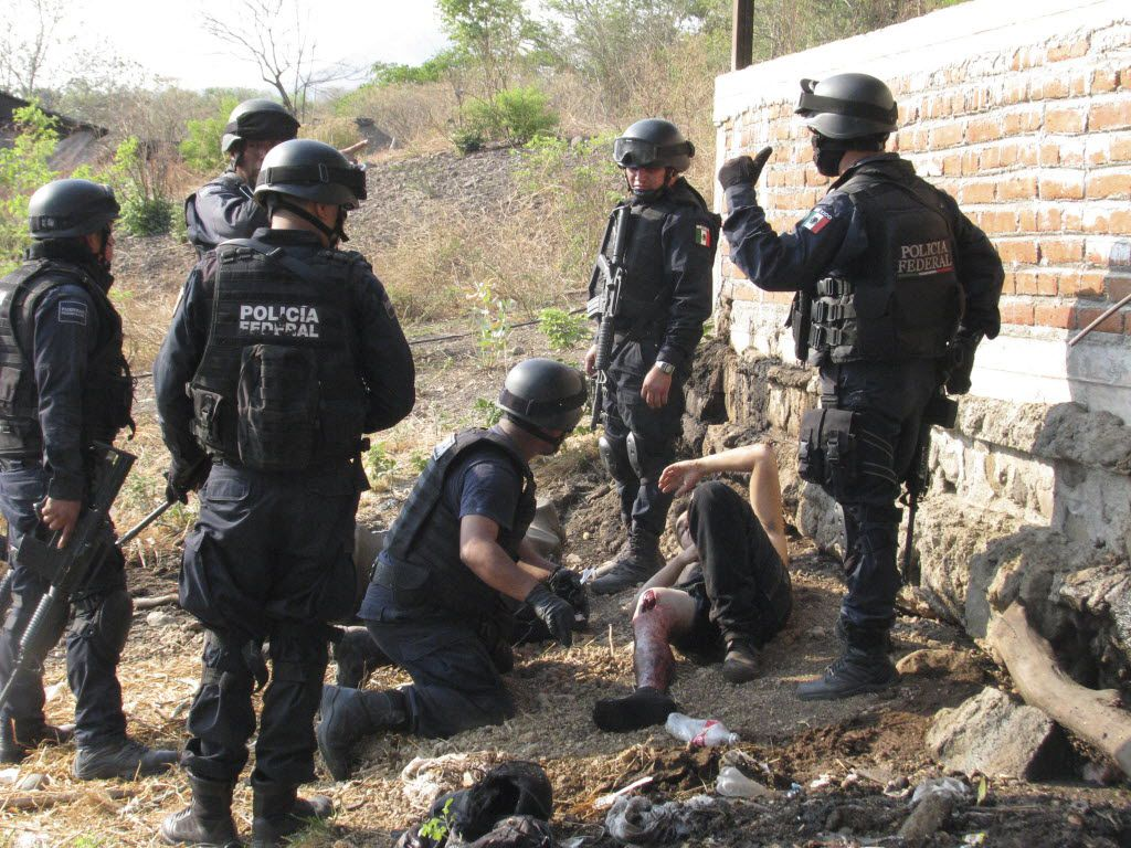 In May 2011, federal police stood over an injured man, allegedly belonging to the La Familia drug cartel, after a gun battle one day earlier in Jilotlan, Mexico.