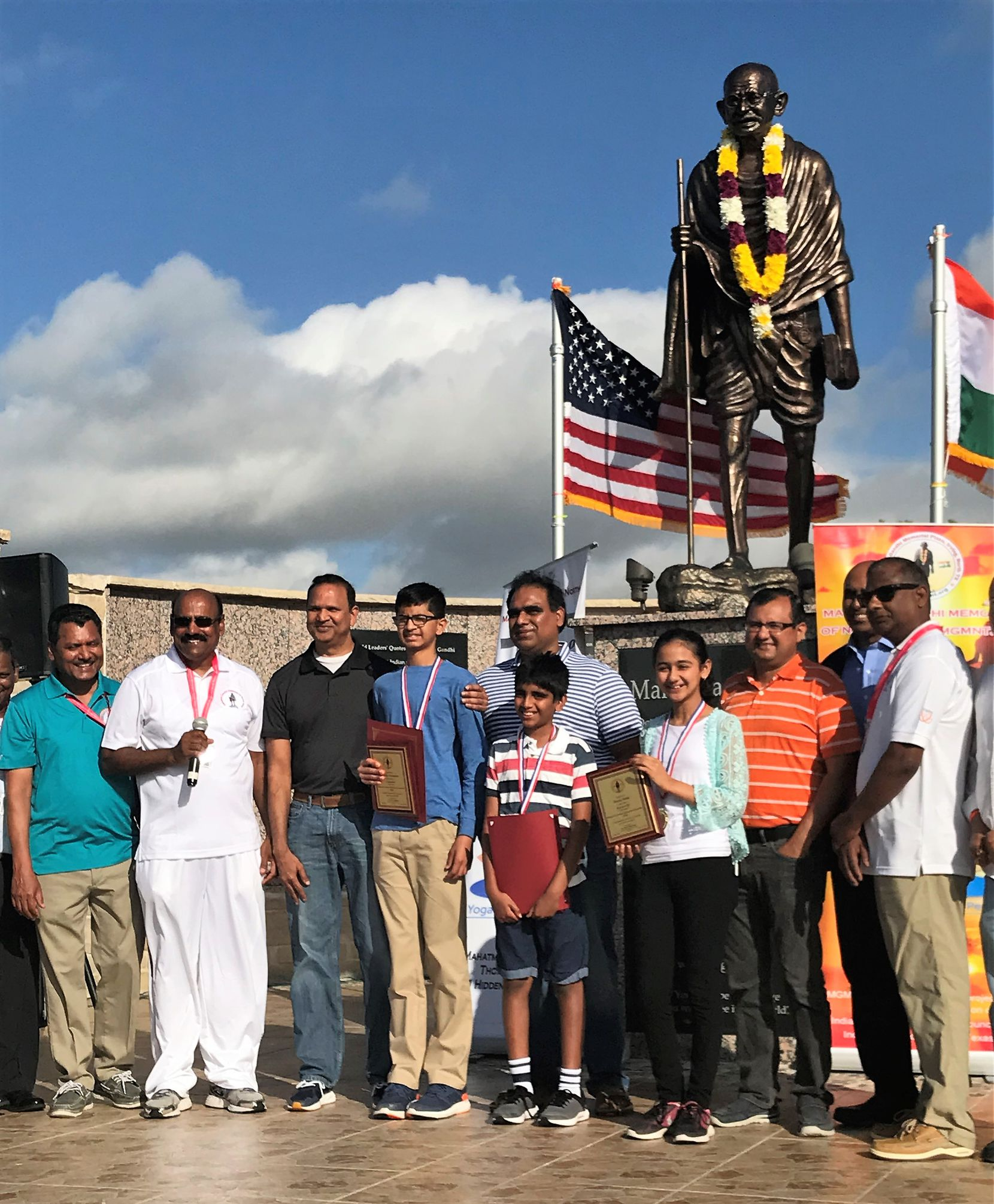 Mahatma Gandhi Memorial officials presented plaques and ribbons to the top three winners of the 2018 Scripps National Spelling Bee who posed with their fathers on Father's Day at the memorial in Irving. The winners are Karthik Nemmani (fourth from left), Abhijay Kodali (with red folder) and Naysa Modi. (Deborah Fleck/Staff)