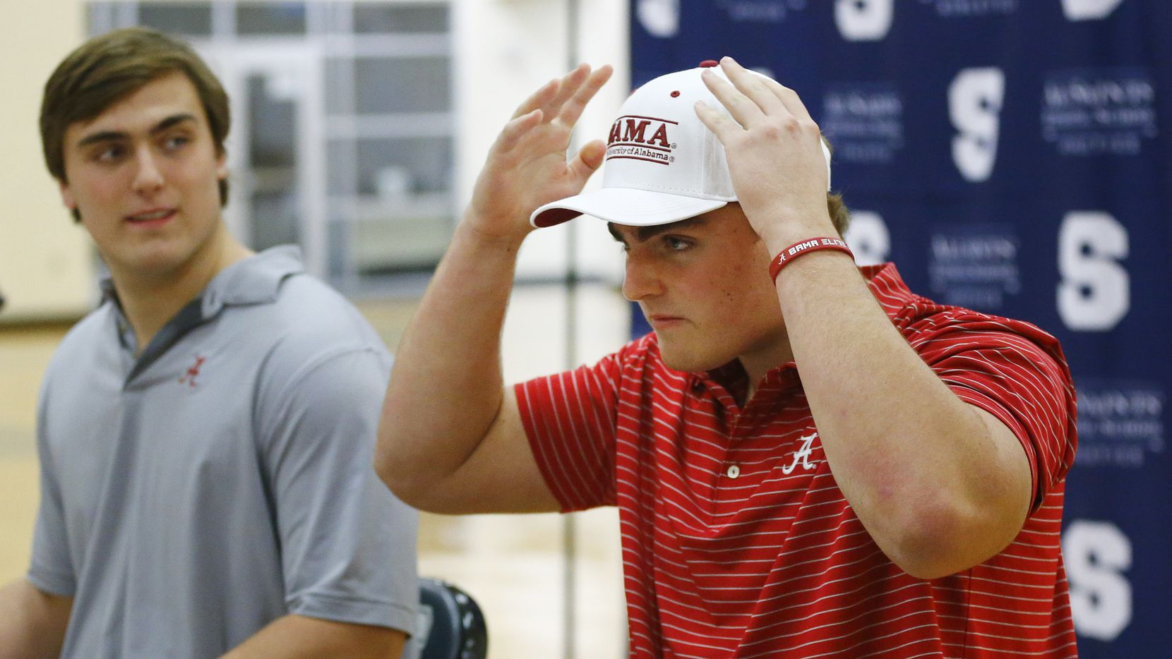 Fort Worth All Saints' Episcopal School James Brockermeyer adjusts his Alabama hat after signing a national letter of intent to play there. Joining him at Alabama is his twin brother Tommy Brockermeyer (left) in the schools gymnasium, Wednesday, December 16, 2020.