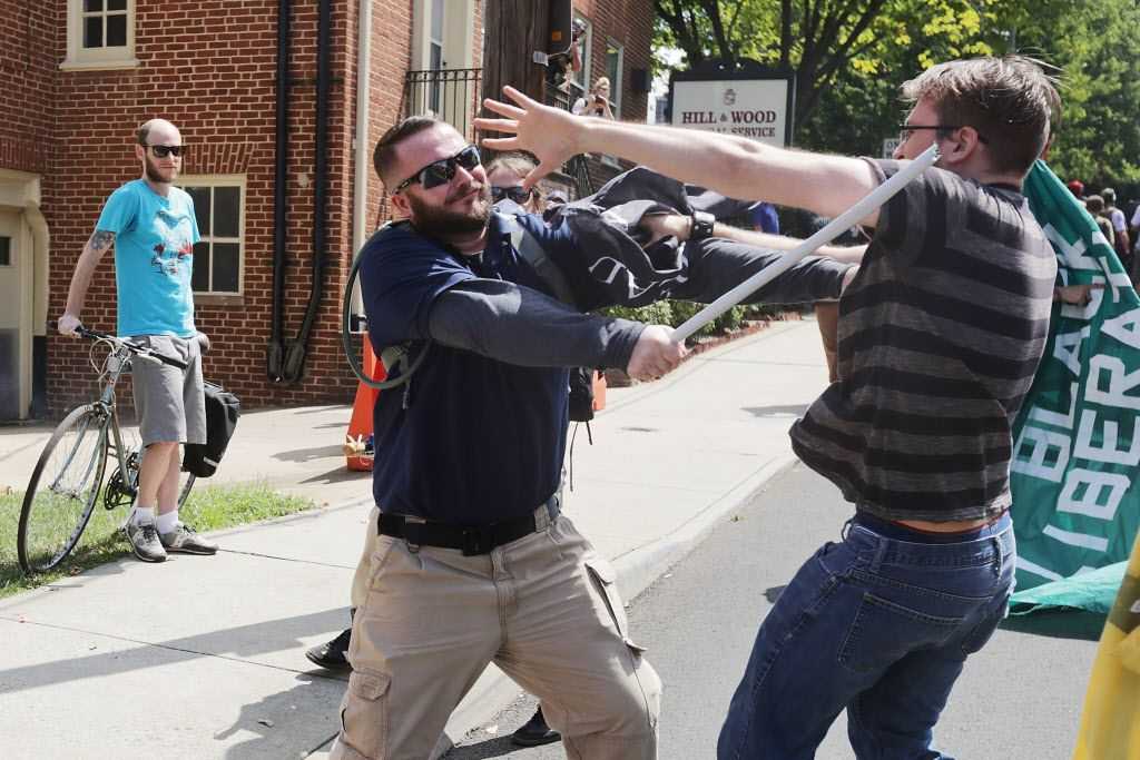 "CHARLOTTESVILLE, VA - AUGUST 12:  White nationalists, neo-Nazis and members of the ""alt-right"" clash with counter-protesters in the street after the ""Unite the Right"" rally was delcared a unlawful gathering by Virginia State Police August 12, 2017 in Charlottesville, Virginia. After clashes with anti-fascist protesters and police the rally was declared an unlawful gathering and people were forced out of Lee Park, where a statue of Confederate General Robert E. Lee is slated to be removed.  (Photo by Chip Somodevilla/Getty Images)"