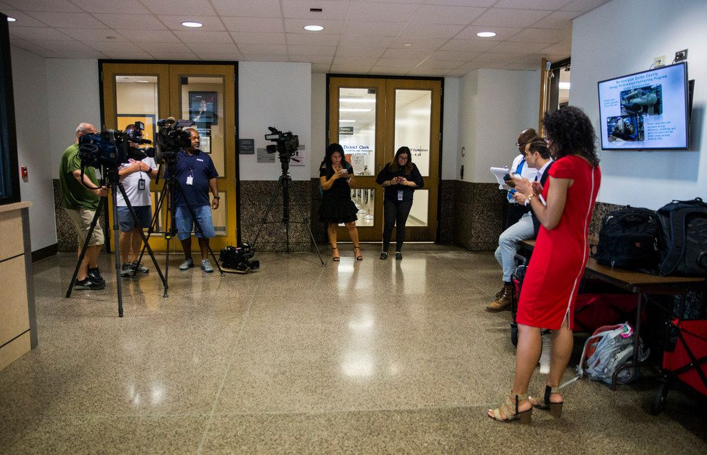 Reporters wait in the hallway outside the Central Jury Room as potential jurors are selected for the Amber Guyger trial on Friday, September 6, 2019 at the Frank Crowley Courts Building in Dallas.  Reporters were briefly not allowed inside the room. (Ashley Landis/The Dallas Morning News)