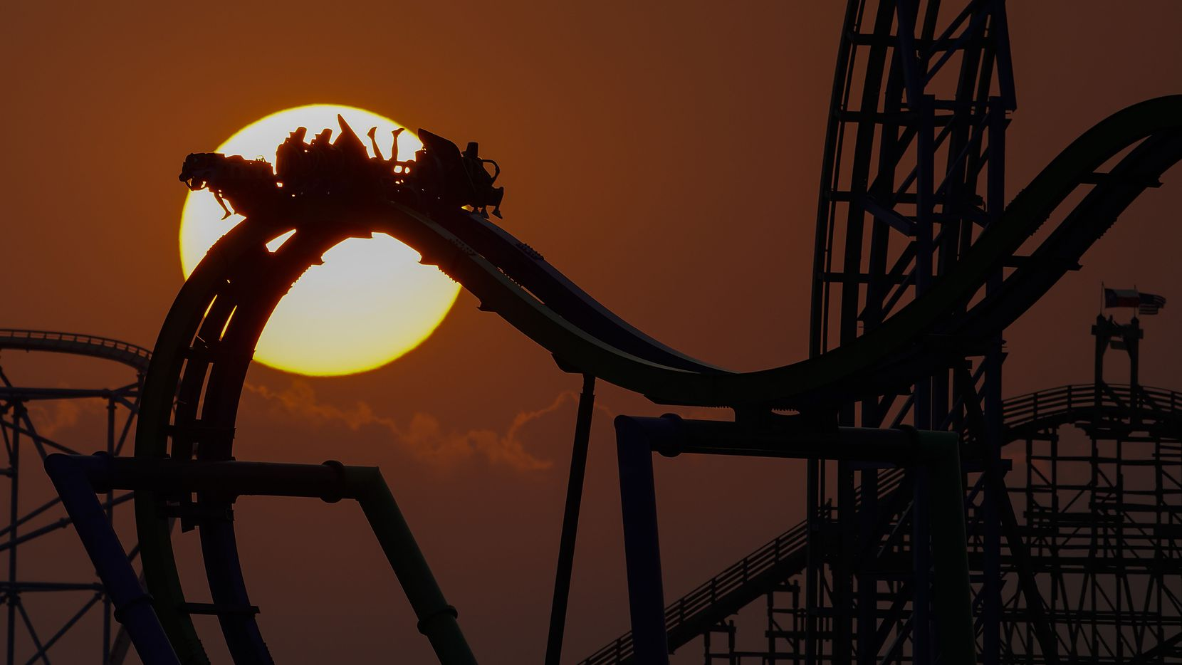 People ride The Joker thrill ride as the sun sets behind Six Flags Over Texas amusement park on Sunday, Sept. 27, 2020.