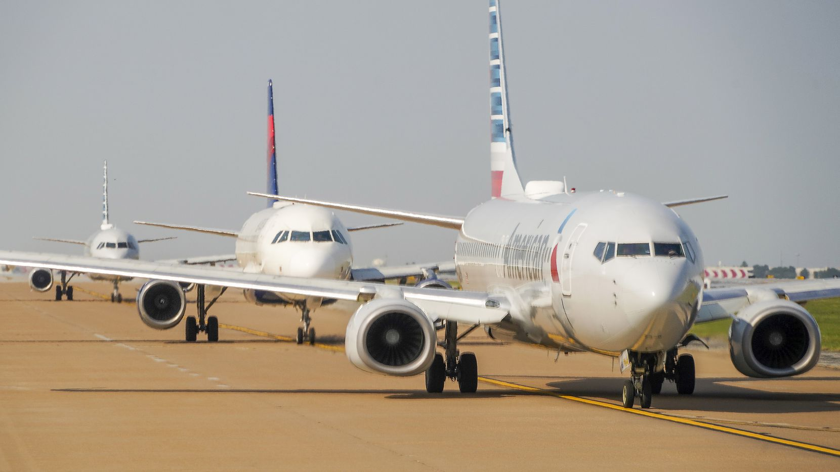 American Airlines and Delta Air Lines jets line up for takeoff at DFW International Airport.