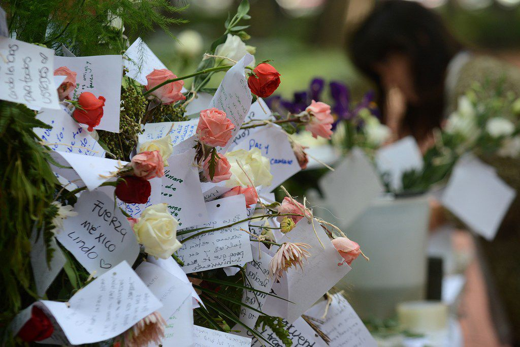 People start a memorial with flowers at a park in front of one of the collapsed buildings in Mexico City on Sept. 23, 2017. In the capital, the quake toppled 39 buildings, mostly in a central area with older construction that is popular with tourists and foreigners living in the city, and also in the south.