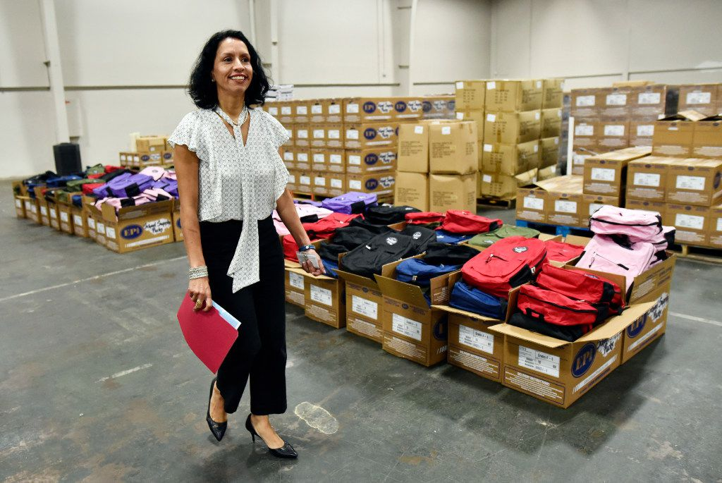 Liz Cedillo-Pereira, the director of the city of Dallas' Office of Welcoming Communities and Immigrant Affairs, stands among backpacks for a recent back-to-school fair for low-income families at Fair Park.