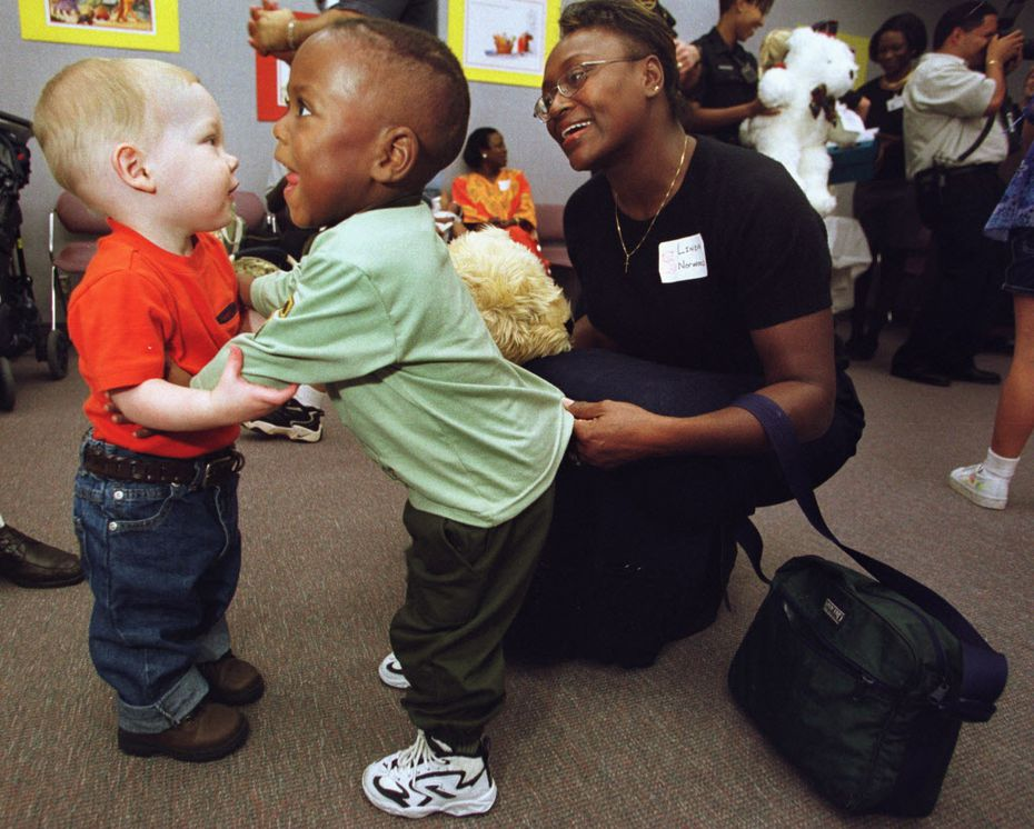 Ethan Housley (left), 16 months, gets a hug from K.L. Norwood, 2, with the help from his mother, Linda, at the 16th annual reunion of the Neonatal Intensive Care Unit at Arlington Memorial Hospital Thursday evening. Ethan and K.L. were patients in the NICU at Arlington Memorial.