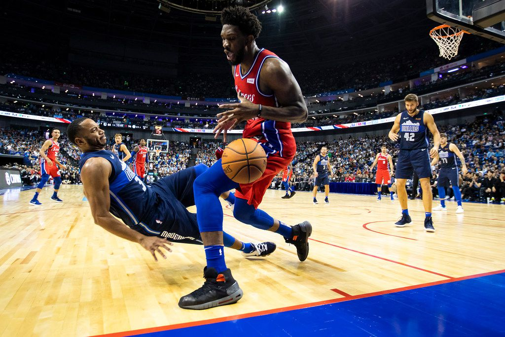 Dallas Mavericks guard Devin Harris (34) is knocked backwards in a collision with Philadelphia 76ers forward Joel Embiid (21) as the ball goes out of bounds during the second half of an NBA China Games 2018 preseason basketball game at Mercedes-Benz Arena on Friday, Oct. 5, 2018, in Shanghai. (Smiley N. Pool/The Dallas Morning News)