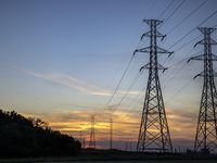 The sun sets behind electricity towers along Mountain Creek Parkway in Dallas on June 30.