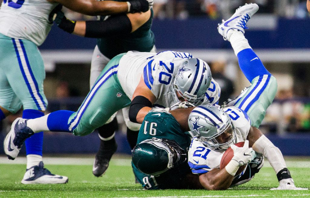 FILE - Cowboys running back Ezekiel Elliott (21) is brought down by Eagles defensive tackle Fletcher Cox (91) during the fourth quarter of a game on Sunday, Oct. 30, 2016, at AT&T Stadium in Arlington. Cowboys guard Zack Martin (70) is at left.