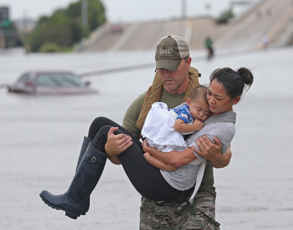 Houston SWAT officer Daryl Hudeck carries Catherine Pham and her son 13-month-old son Aiden to safety after they were rescued via boat from the flooding on Interstate 610 south in Houston on Sunday. (Louis DeLuca/The Dallas Morning News)
