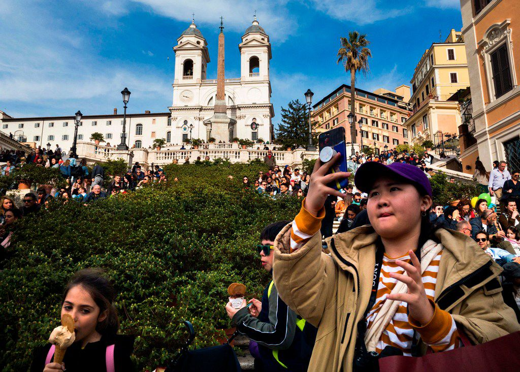 A tourist takes a photo with her smartphone as people sit on the Spanish Steps in Rome.