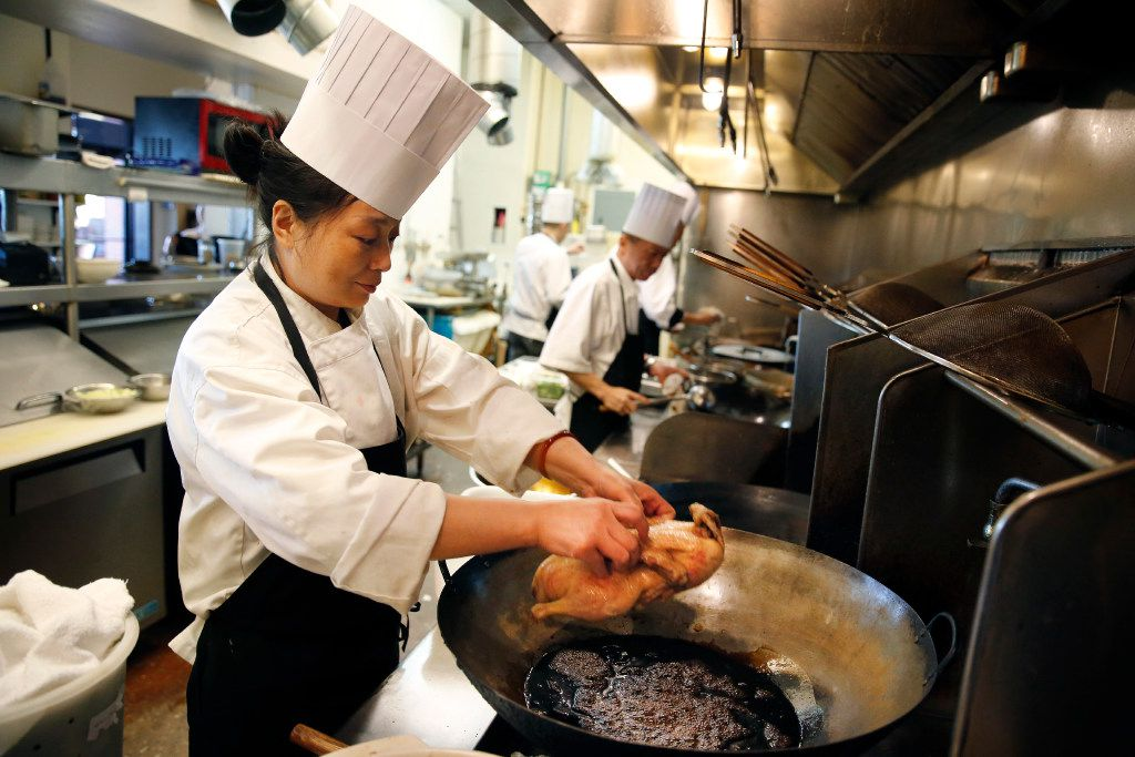 Chef Li Zheng Wang cooks a whole duck at Fortune House. (Tom Fox/The Dallas Morning News)