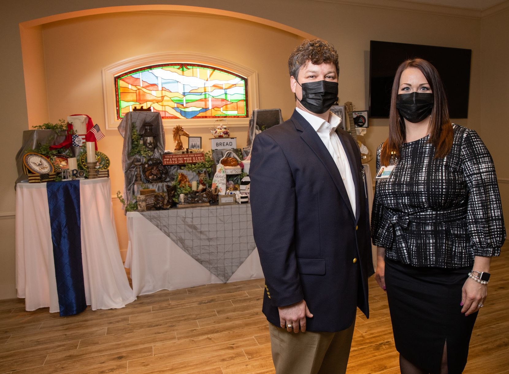Sam Scott and Kristine Reed in front of the life story display at Ted Dickey West Funeral Home in Dallas.