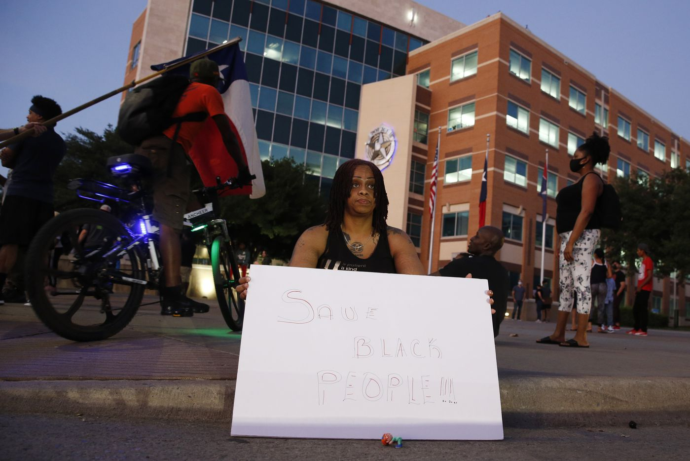 Chanel Speight of Dallas sits in front of the Dallas Police Department Headquarters during a demonstration against police brutality in downtown Dallas, on Friday, May 29, 2020. George Floyd died in police custody in Minneapolis on May 25.