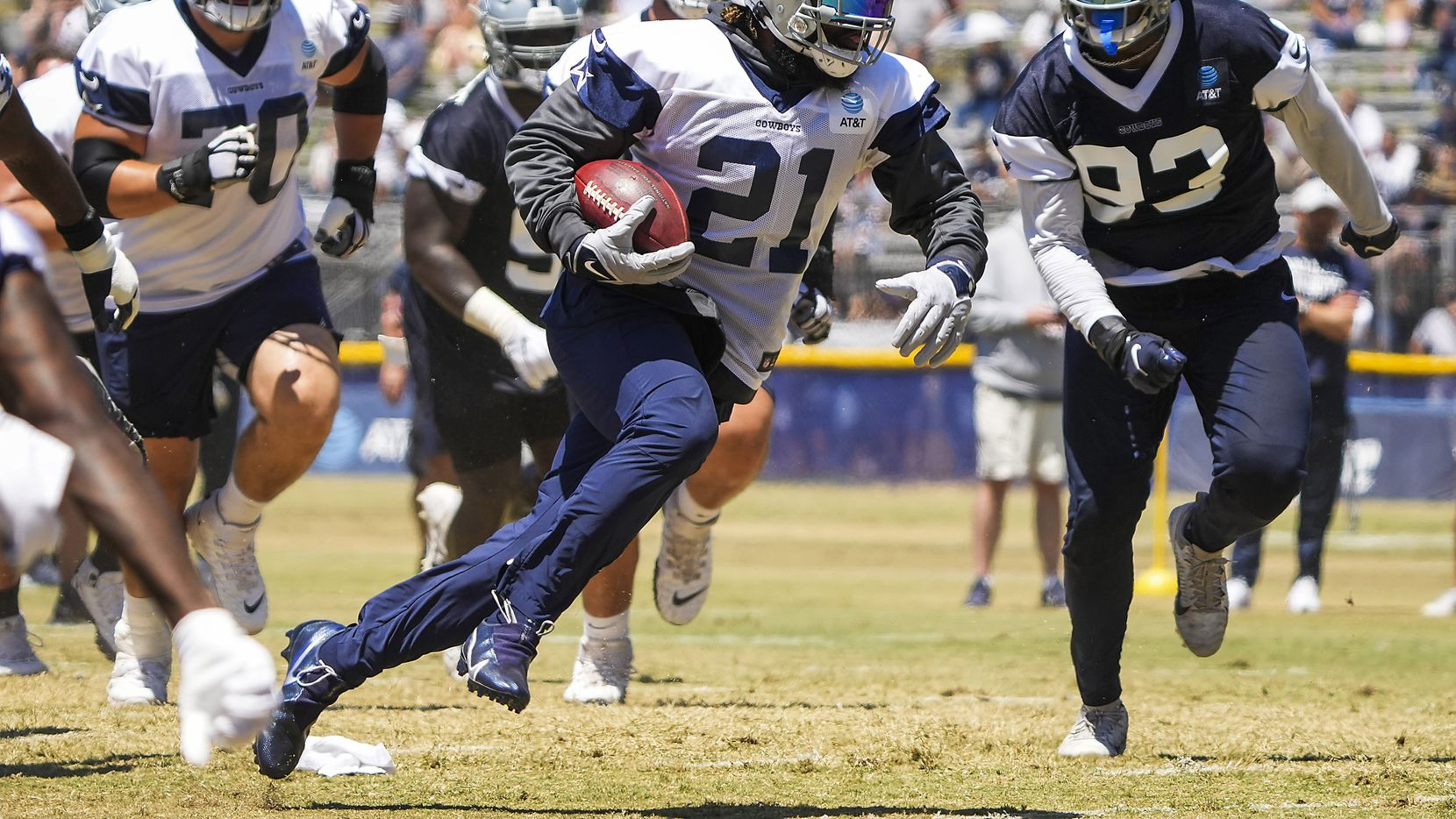 Dallas Cowboys running back Ezekiel Elliott (21) runs into the end zone past defensive end Tarell Basham (93) during a practice at training camp on Tuesday, Aug. 3, 2021, in Oxnard, Calif.