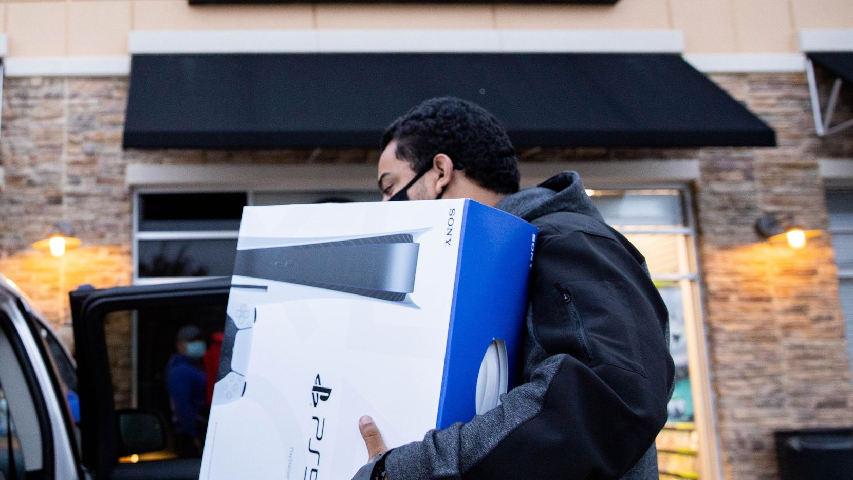 Brandon Lopez of Irving loads his new Playstation 5 in his car on Black Friday at the Timber Creek Crossing GameStop.
