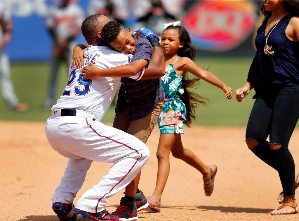 Texas Rangers Adrian Beltre (29) hugs his son Adrian Jr. and daughters Canila and Cassandra (right) after they dropped the banner on his 3,000 career hit in the fourth inning at Globe Life Park in Arlington, Sunday, July 30, 2017. (Tom Fox/The Dallas Morning News)