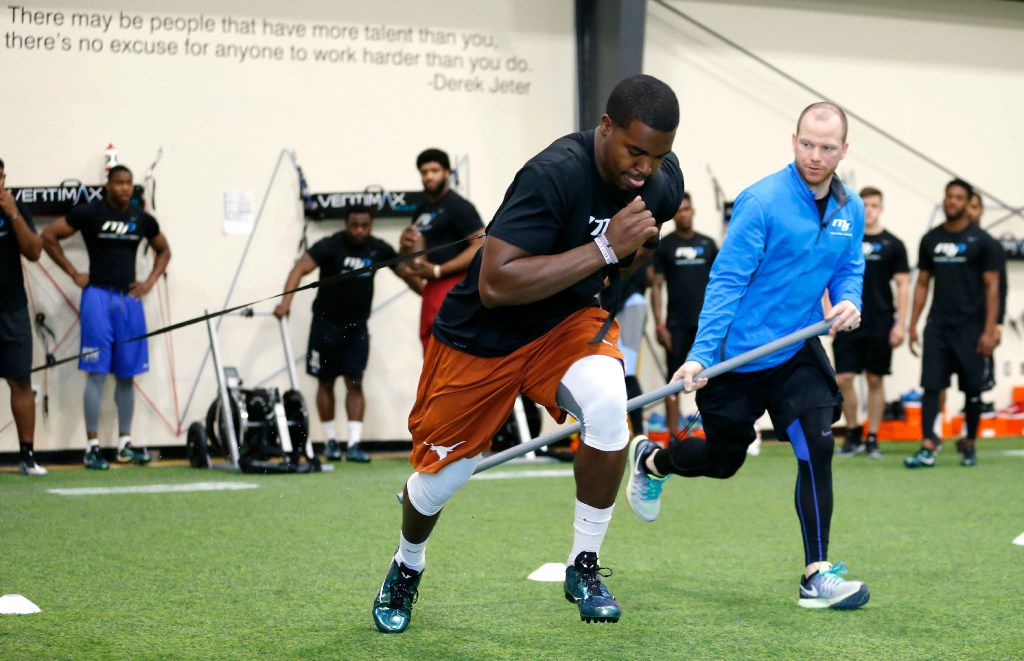 Texas' Tyrone Swoopes sprints down the field as High Performance Coordinator Brian Abadie observes him during MJP Media Day at Michael Johnson Performance in McKinney on Wednesday, February 22, 2017. Numerous athletes prepare for pro day and the upcoming NFL Combine. (Vernon Bryant/The Dallas Morning News)