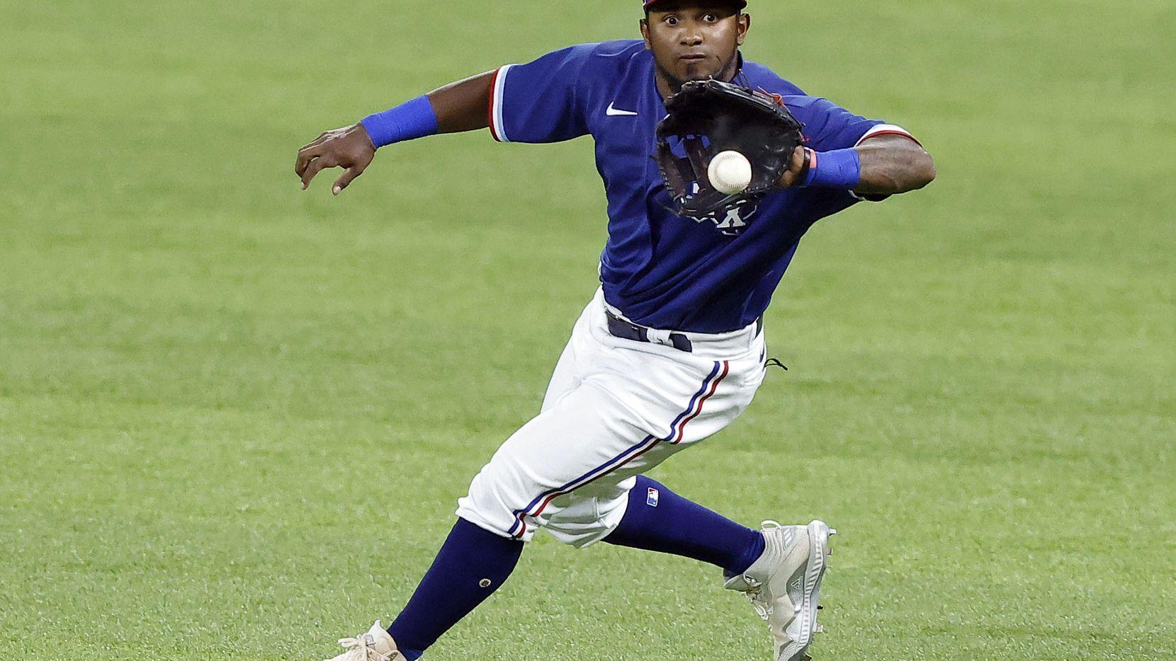 El jugador de los Rangers de Texas, Yonny Hernández, atrapa una pelota en el partido de exhibición contra los Brewers de Milwaukee en el Globe Life Field, el 30 de marzo de 2021.