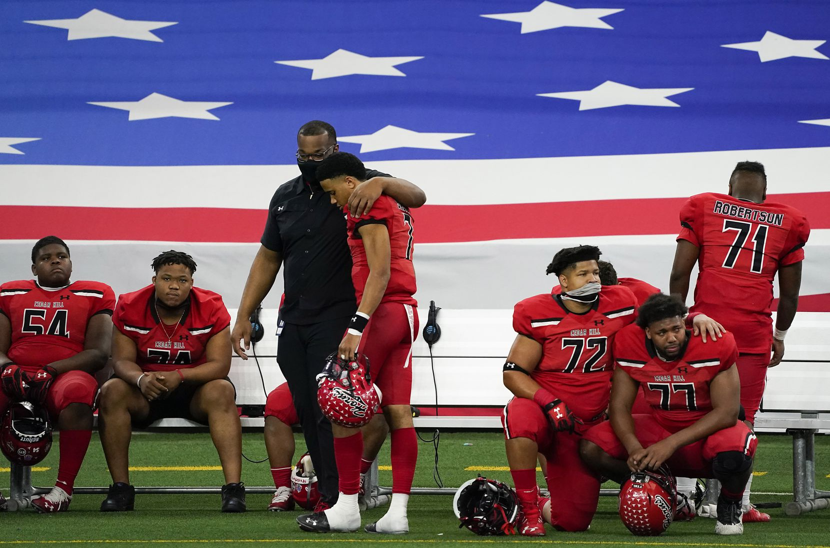 Cedar Hill quarterback Kaidon Salter (7) is consoled by a coach as teammates Matthew Worth (54), Carlos Peoples (74), Josiah Jefferson (72), Miquel Massey, Jr (77) and Ivan Narro (71) wait for the final moments to tick off the clock in a loss to Katy in the Class 6A Division II state football championship game at AT&T Stadium on Saturday, Jan. 16, 2021, in Arlington, Texas. Katy won the game 51-14.