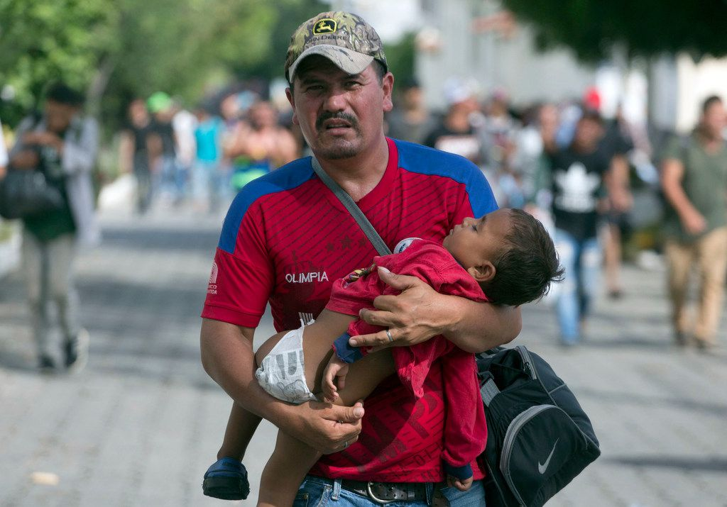 A Honduran migrant carries his son as he walks toward the U.S., in Chiquimula, Guatemala, Tuesday, Oct. 16, 2018. President Donald Trump threatened on Tuesday to cut aid to Honduras if it doesn't stop the impromptu caravan of migrants, but it remains unclear if governments in the region can summon the political will to physically halt the determined border-crossers.