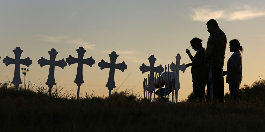 Irene and Kenneth Hernandez and their daughter Miranda Hernandez say a prayer in front of some of the 26 crosses placed in a field in Sutherland Springs, Texas to honor those who were killed in Sunday's mass shooting, when a gunman opened fire at a Baptist church in the small town southeast of San Antonio. Photographed on Monday, November 6, 2017. (Louis DeLuca/The Dallas Morning News)