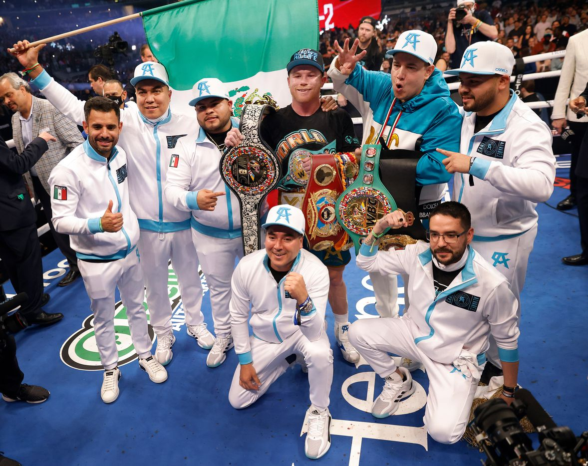 Boxer Canelo Alvarez (center) poses for a photo with his team and belts after defeating Billy Joe Saunders for the WBC super middleweight title  at AT&T Stadium in Arlington, Saturday, May 8, 2021. (Tom Fox/The Dallas Morning News)