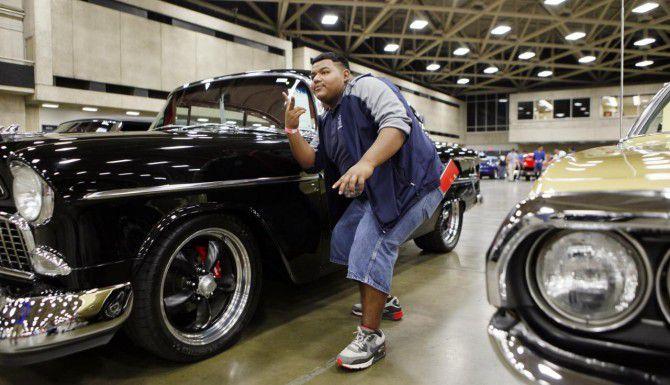 El estudiante de la preparatoria W.H. Adamson, Jorge Martínez, posa con un Chevrolet Bel Air de 1955 en una subasta de autos de colección y antigüos. Mecum Auctions estará en Dallas hasta el sábado. (ESPECIAL PARA AL DÍA/BEN TORRES)