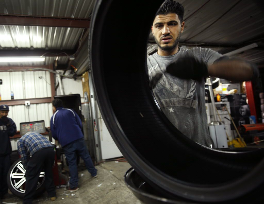 Tire tech Danny Hossin (right) cleans a new tire at Omar Omar's tire shop in Pleasant Grove.